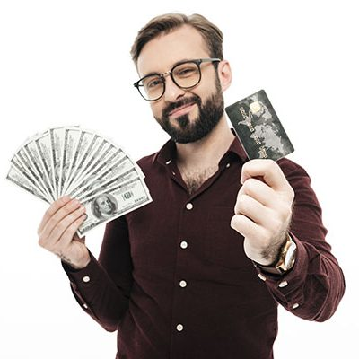 Photo of cheerful happy thinking young man standing isolated over white background. Looking camera holding money and credit card.